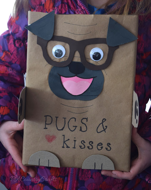 Pugs and Kisses Valentine box made out of a cereal box and kraft paper.