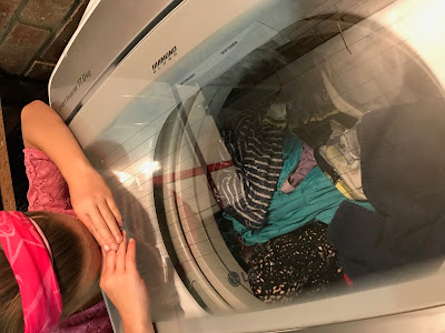 Girl looking into LG Smart Inverter Top Loader Washing Machine while washing