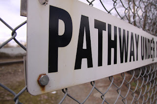 "A sign on a fence that says ""Pathway Under..."""