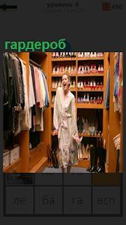 В шикарном гардеробе стоит девушка и радостно улыбается