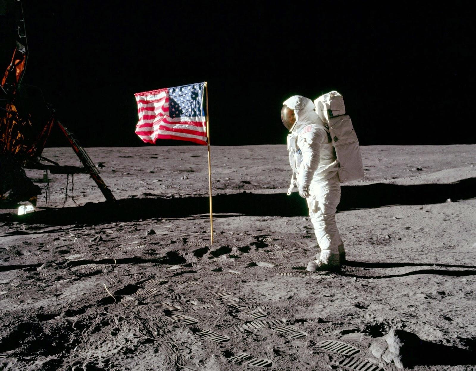 Una foto lunare con un astronauta americano di fronte alla bandiera.