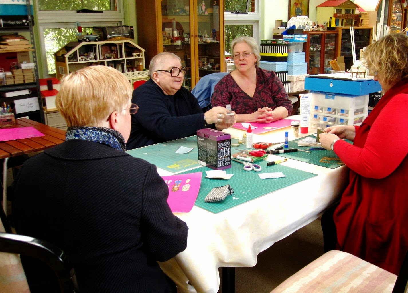 Group of four women around a workshop table, looking at bits of a miniature picnic basket kit.