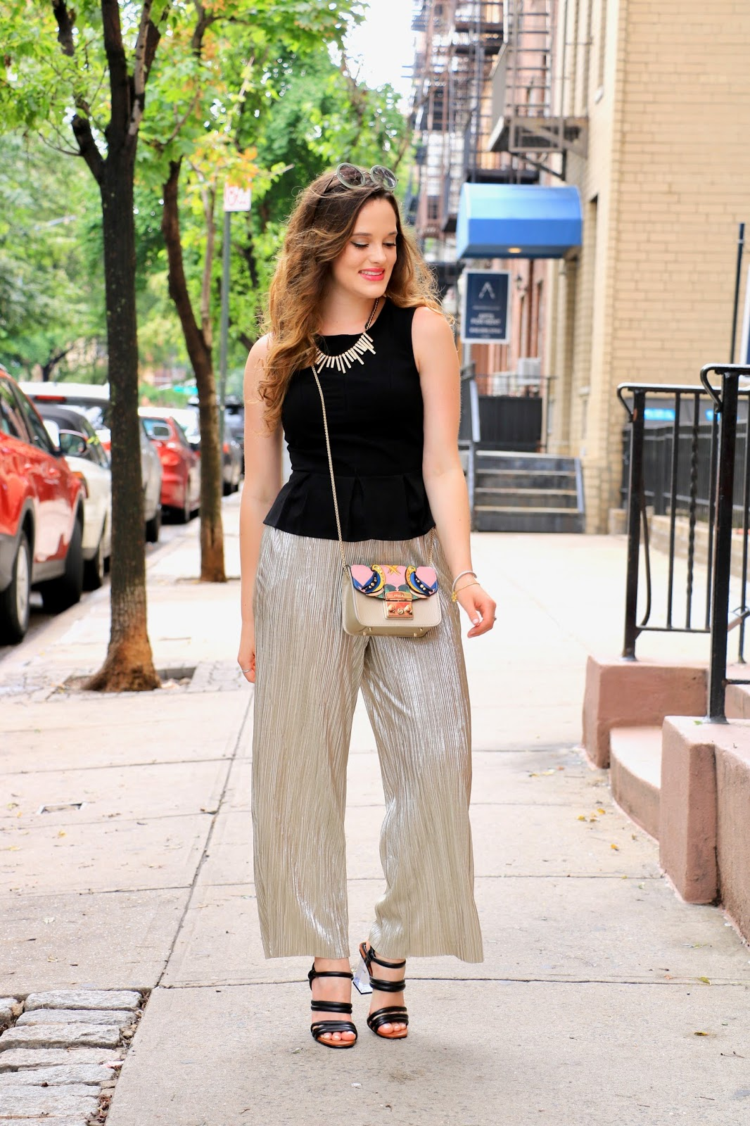 nyc fashion blogger Kathleen Harper wearing gold flowy pants and a black peplum top
