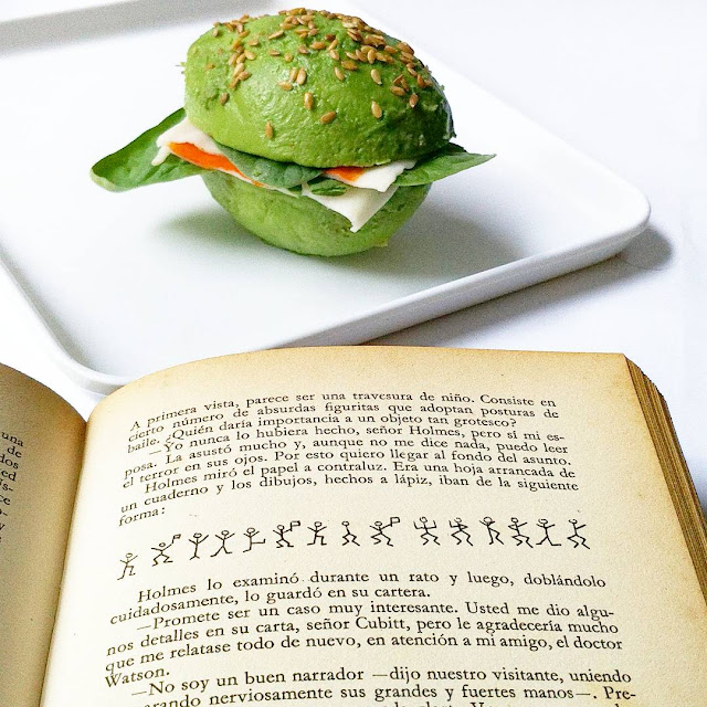 visulmente las dos mitades de un aguacate, con sesamo por envima y el relleno de lechuga y tomate dan la sensación de ser una hamburguesa verde