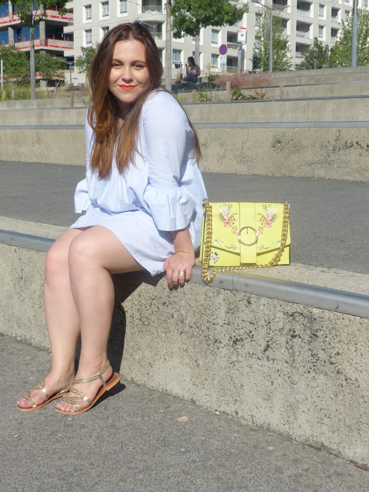 Look estival, sac jaune fleuri et robe combinaison bleue.