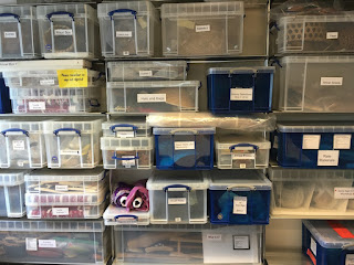 Several plastic boxes stacked on shelves