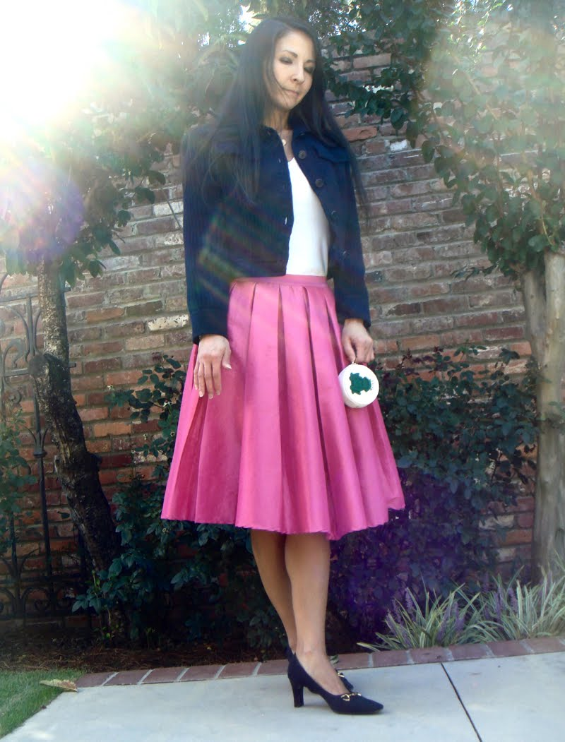 Wearing blue shacket over white tee with full pink skirt and blue heels. Holding small coin purse with frog.