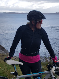 woman with road biking standing with sea and island background