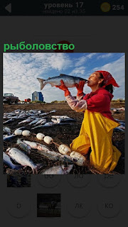 На берегу много рыбы и сеть для рыболовства, мужчина собирает рыбу