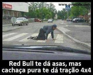 Foto tirada de dentro de um veículo em uma rua com poucos carros. Um homem engatinhando, atravessa na faixa de pedestres. Abaixo a frase: Red Bull te dá asas, mas cachaça pura te dá tração 4X4.