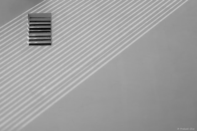 A Black and White Minimal Art Photograph of a Window with Horizontal Blinds, placed on a White Wall with Diagonal lines created by Light and Shadows