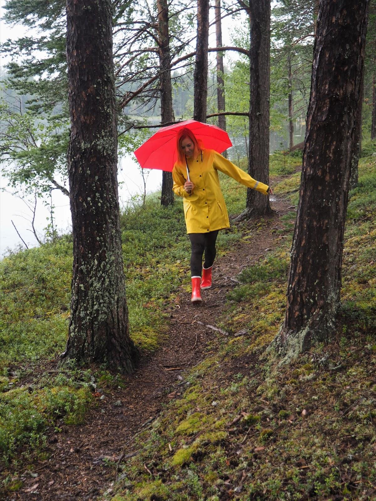 Punainen sateenvarjo, keltainen sadetakki, metsässä, kuvaaja Fia Hollmén