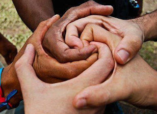 Hands of different sizes and skin tones wrapped spiralwise around each other
