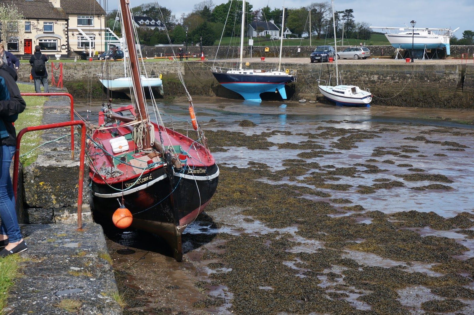 Kinvara Harbour on low tide with boats resting on walls