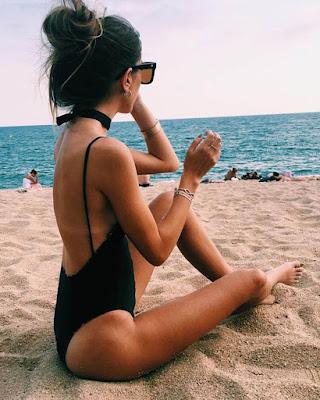 pose sentada en la playa tumblr con traje de baño negro