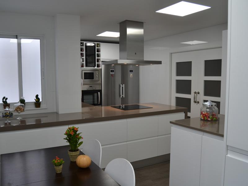 Gran cocina de muebles blancos y encimera marrón