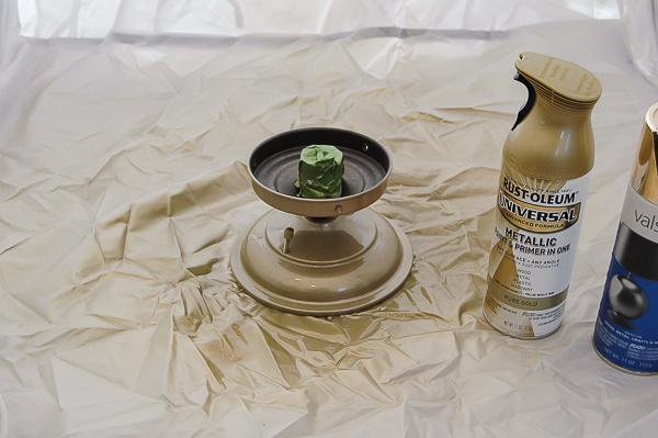 Spray painting gold paint on light fixture