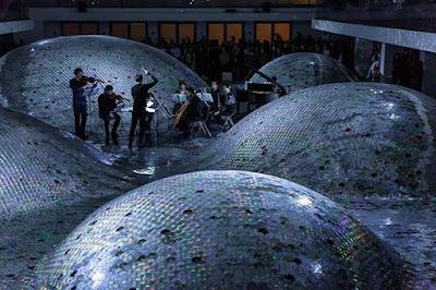 Orquesta tocando en escenario con Cds reciclados