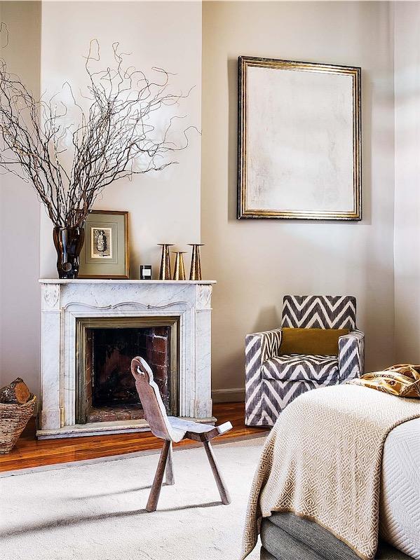 chimenea clasica y junto a ella butaca tapizada con tela en zigzag chicanddeco