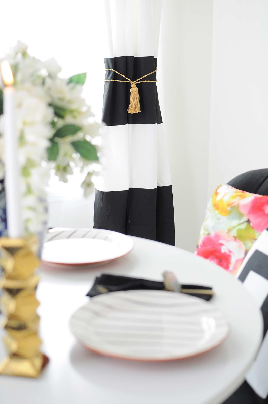 Black and white striped curtains with gold tassels in a small dining room space makeover.