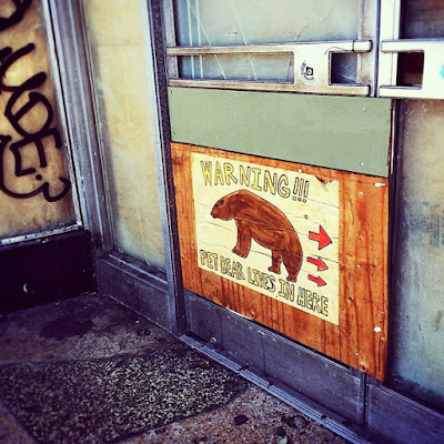 "sign on old graffitied building reading ""warning!!! pet bear lives in here!"""