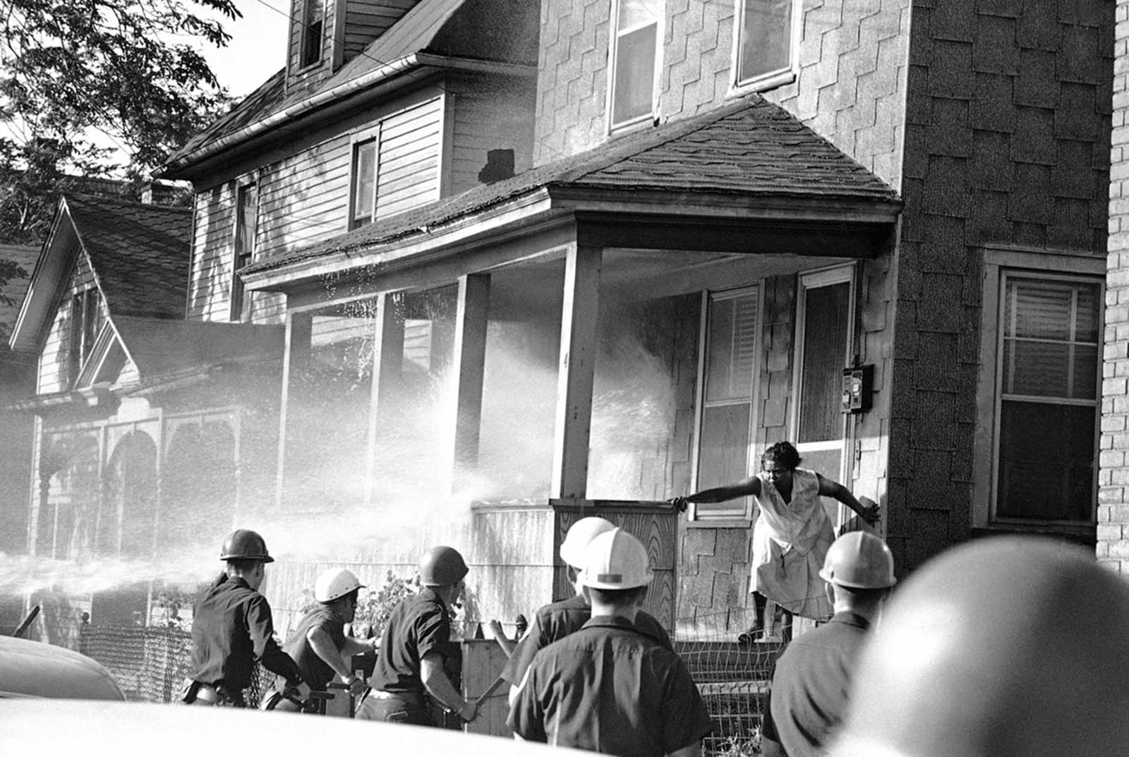 This is the beginning of a clash between African Americans and police officers in Rochester, New York, July 27, 1964. Fire hoses turned on house's porch. A woman stands her ground as companions duck behind porch's wall.