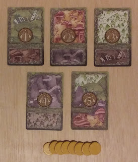 On top, five cards representing the rituals and their blessed or cursed terrain types from Fae. On the bottom, a row of plain yellow discs, about the size of pennies, from Clans.