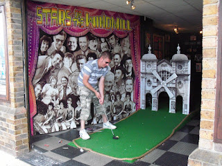 Playing one of the partially outdoors holes at the indoor Crazy Golf course found within the old Windmill Theatre in Great Yarmouth