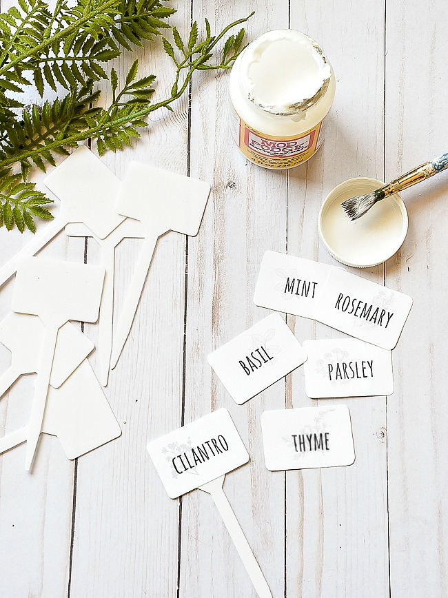 Gluing herb printable labels to Dollar Tree garden markers