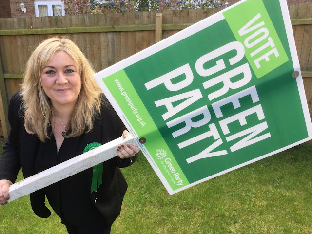 Julie holding vote Green banner