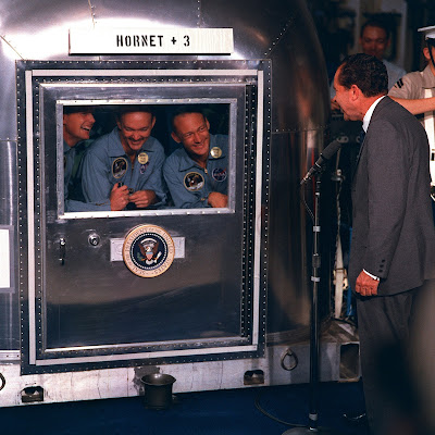 "Apollo 11 flight crew members Neil A. Armstrong, Michael Collins, and Edwin E. ""Buzz"" Aldrin, Jr., inside the Mobile Quarantine Facility (MQF), being greeted through the window by President Richard M. Nixon; July 24, 1969."