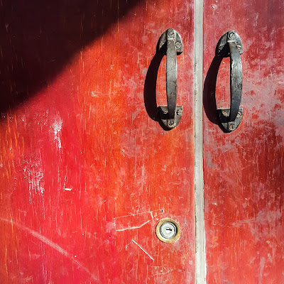A Minimalist Photo of two metal handles of red door shot by Samsung Galaxy S6 Smart Phone