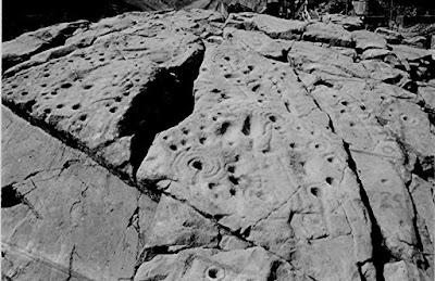 """Местность представляет из себя огромное скальное каменное образование с сотнями узоров и рисунков """"выдавленных"""" в камне петроглифы  Петроглифы состоят из спиралей, колец линий и фигур, типичные рисунки на мегалитах тысячелетний давности, подобные можно найти по всей Европе и на других континентах.  Камень открыт археологом Rev James Harvey в 1887 году"""