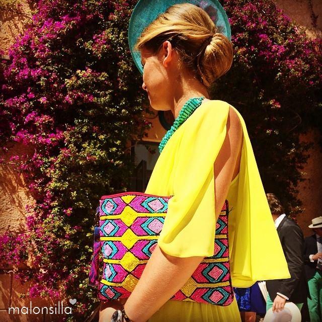 Invitada a boda de perfil con tocado y recogido bajo, bolso estampado geométrico en amarillo, fucsia y turquesa