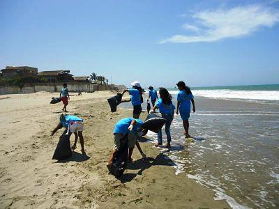 Cuidar las playas. Personas recogiendo basura de la playa
