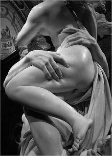 Foto em preto-e-branco de parte de uma escultura em mármore de Bernini. Proserpina, nua, apoiada em Hades que a sustenta acima dos ombros. A mão direita de Hades apalpa fortemente a coxa de Proserpina que está com o corpo de perfil à esquerda, perna esquerda levemente sobre a outra fazendo sombra sobre o joelho direito; o delicado pé esquerdo, posicionado para baixo está no ar; a outra mão de Hades apalpa a cintura e o dedo indicador afunda sobre a carne. No topo, parte das pontas dos cachos dos cabelos ao vento, nas costas, uma sombra contrasta o brilho de um foco de luz sobre o ombro e parte do braço em ângulo a frente do corpo deixando a mostra o delineio de parte do seio esquerdo próximo aos cabelos ondulados de Hades. Entre os dois, um manto com dobras, pregas e ondulações. No teto, uma pintura com duas figuras humanas.