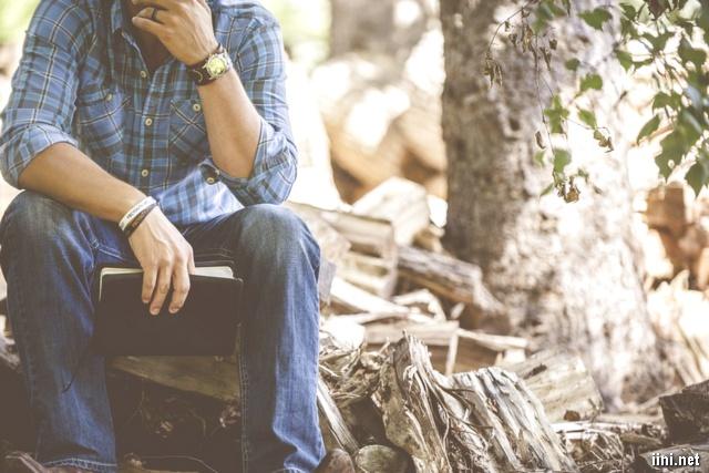 ảnh chàng trai ngồi đọc sách và suy tư