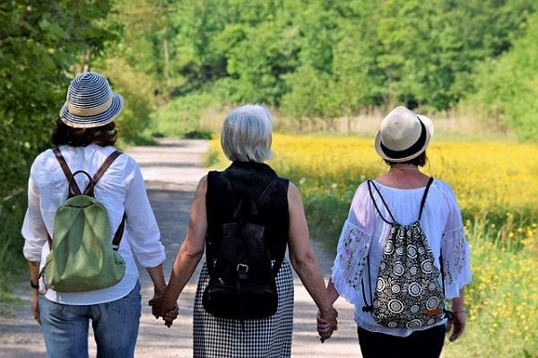 Imagem de três pessoas de mãos dadas caminhando por uma estrada