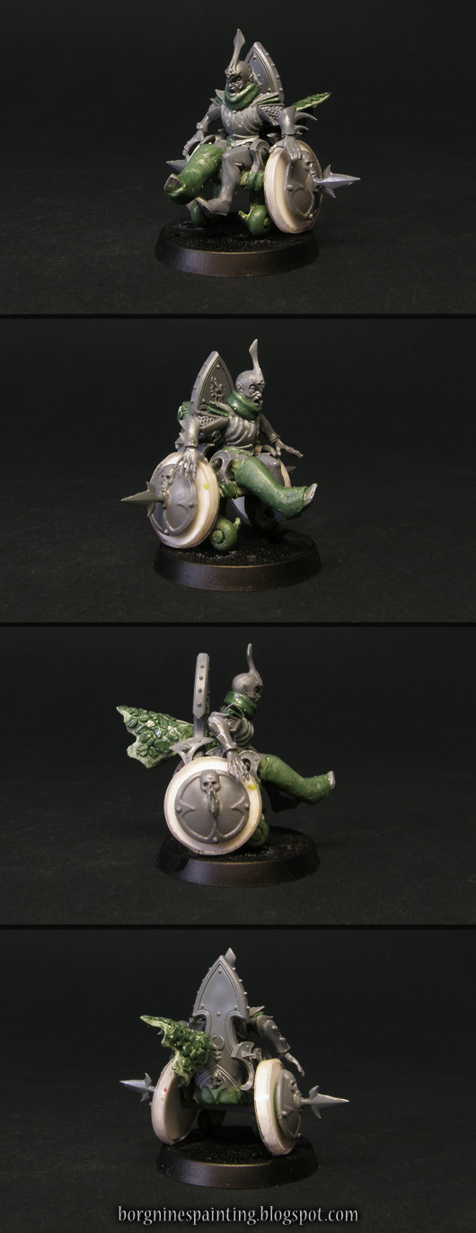 A kitbash/conversion of an injured Dark Elf player miniature riding in a custom-built wheelchair. He has a leg and neck in a cast and is angrily riding forward, with a piece of greenstuff dragon skin flowing behind him.