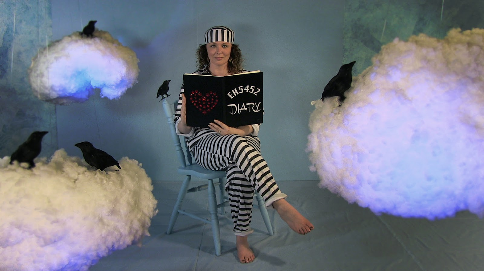 still shot from video artwork, the artist dressed in striped prison garb sits among clouds and black birds reading a diary.