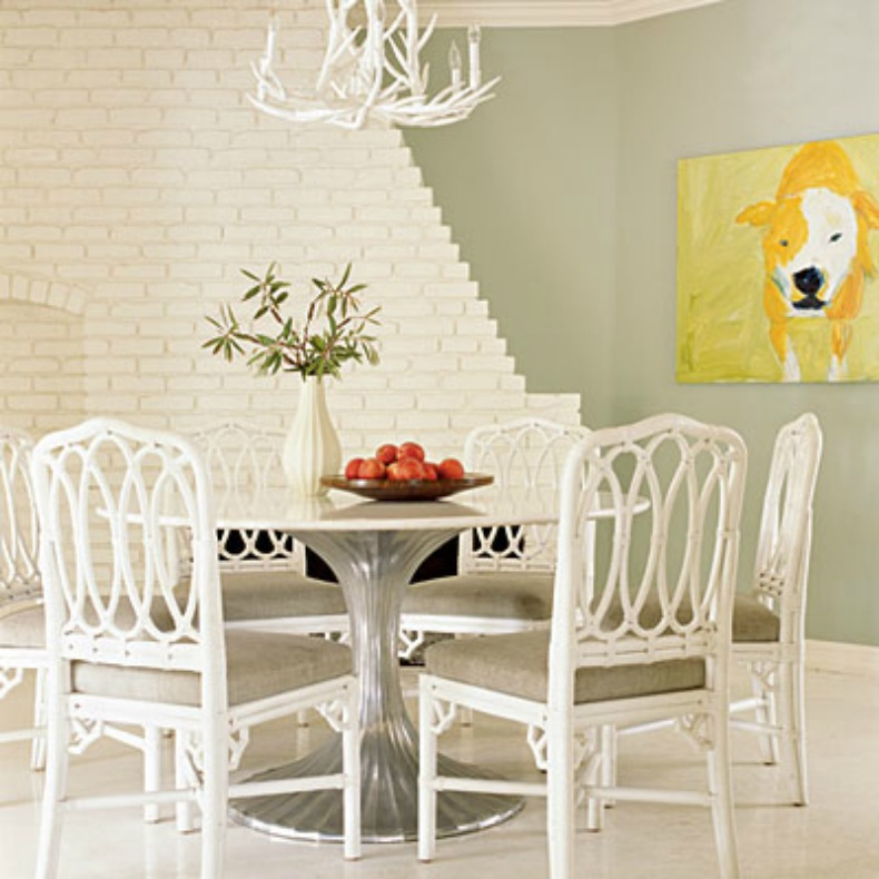 Coastal dining room with white wicker chairs and coral branch chandelier