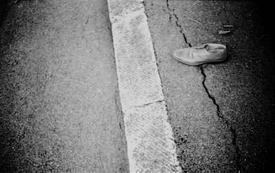 A discarded shoe beside a line in the road