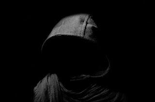 jovem de capuz no escuro