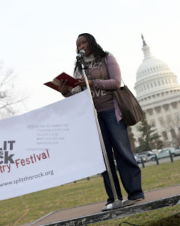 Image of a Black woman with braided hair at a microphone reading a poem from a book on a stage in front of the Capitol. To her left is part of a banner for Split This Rock Poetry Festival.