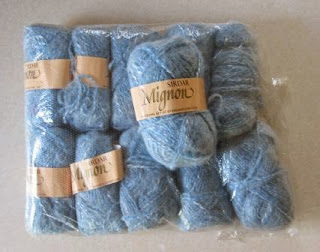 Eleven light blue skeins of Sirdar 'Mignon' - 10 skeins in a packet with 1 on top.