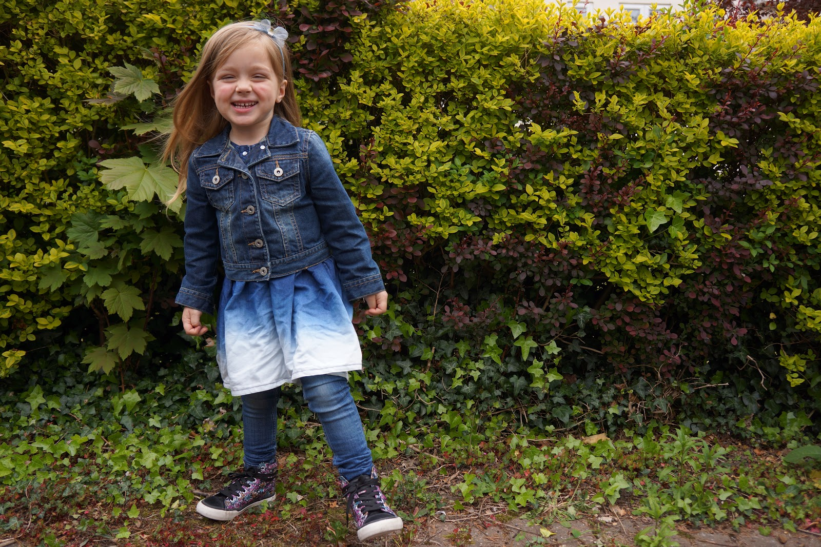 smiling four year old in a triple denim outfit