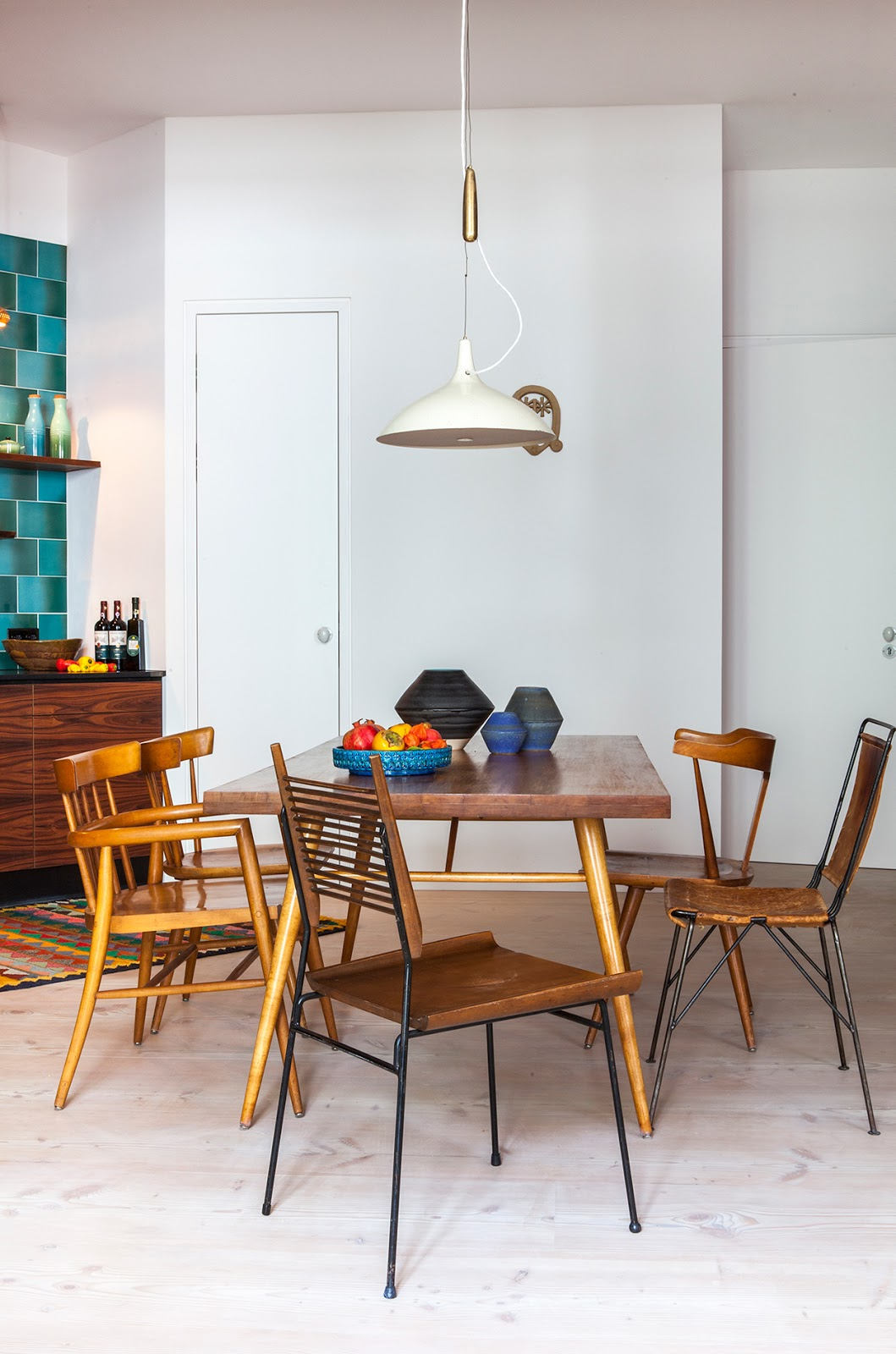 beautiful designer loft in Berlin, colorful 60s kitchen decor, pottery collection, colorful rug, dining table, mid century modern furniture
