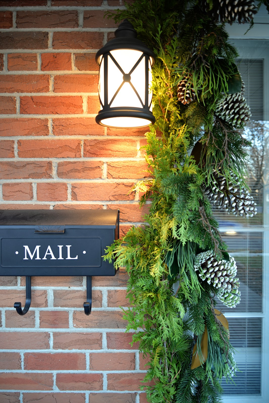 red brick classic house, christmas garland around door, coastal outdoor lighting, mailbox with decal