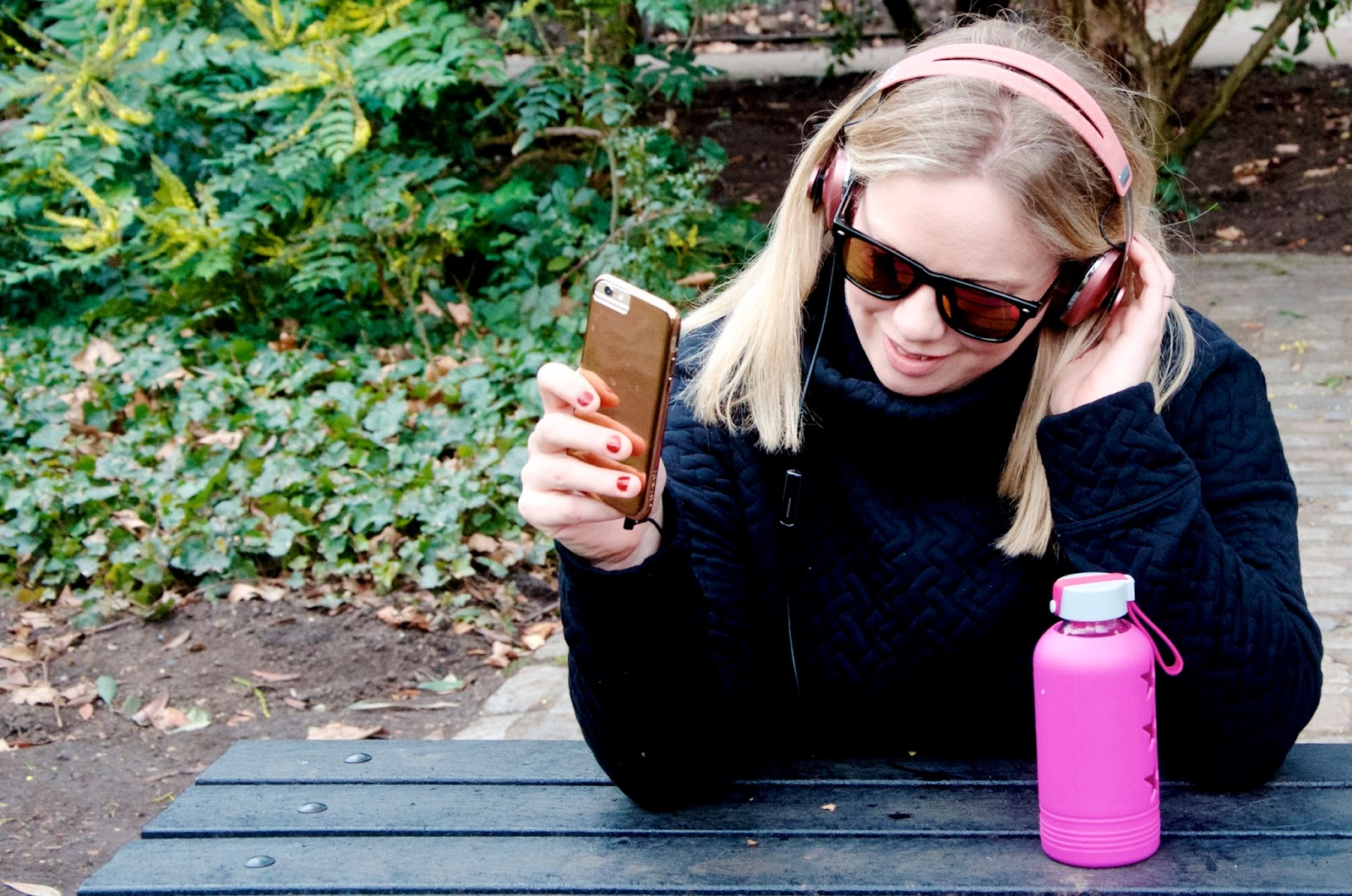 Pink water bottle, pink headphones, wayfarer sunglasses and black quilted sweatshirt