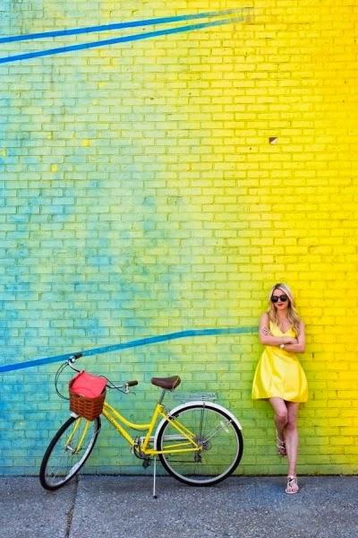 Jeune fille en robe jaune avec vélo